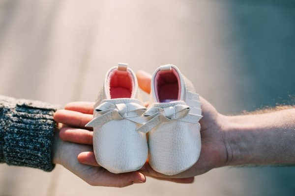 father and mother holding baby's first shoes in their hands, baby naming ceremony by interfaith officiant in florida
